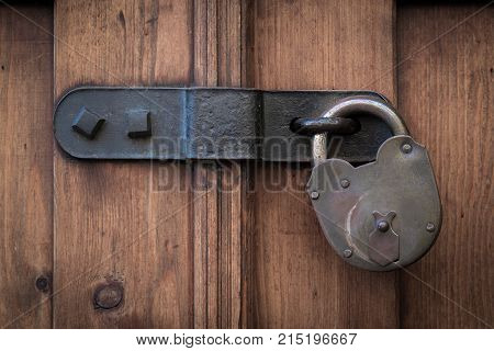 Old wooden door with steel heavy padlock hanging on a door latch