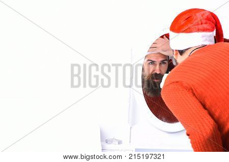 Santa Claus Looks Into Mirror. Man With Beard And Hat