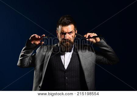 Man With Long Beard Holds Shaving Razor And Scissors.