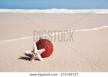 an elegant red christmas ball and a starfish in the sand of a beach, next to the seashore