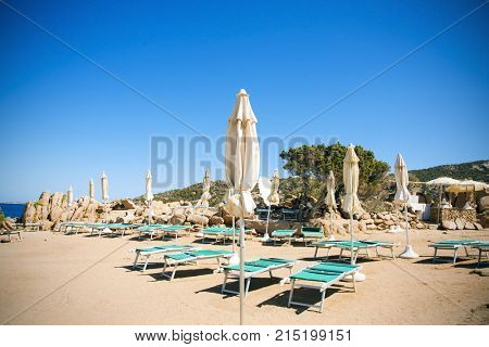 some sunloungers and umbrellas in a beach in Baja Sardinia, Sardinia, Italy