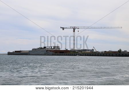 Cranes And Large Construction Site In The Sea For Building A Dam