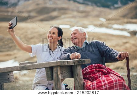 Smiling caregiver nurse and disabled senior patient using digital tablet outdoor