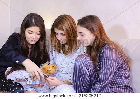 Three wonderful women together hold fashionable women's magazine in their hands and read articles or view bright pictures, eat potato chips, chat and gossip, sitting on gray sofa in bright bedroom at night. European-looking girl with medium-length fair-ha