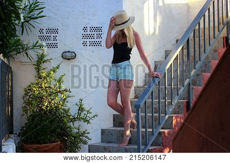 Young beautiful blonde girl holding a hat with her hand on her head and descending from the steps.