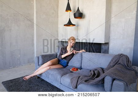 Pretty girl rests from bustle of city and sits on Internet with mobile phone, looks ahead and tries ripe red strawberry berries, sits on gray soft sofa in stylish living room with gray walls. Young European-looking woman with blond hair