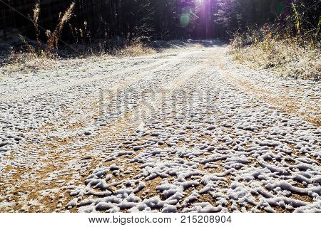 Winter icy slippery dirt road. Forest road after threat of cold weather and snow. The texture of the snow surface.