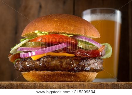 A juicy delicious cheeseburger with bacon lettuce tomato red onions and pickle with a glass of beer.