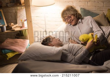 Portrait of smiling grandmother laying in bed with little grandson and telling him bedtime stories