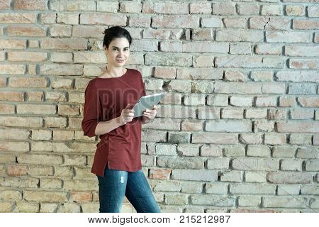 Happy young adult woman standing at wall using tablet smiling. Lifestyle portrait photo with copyspace.