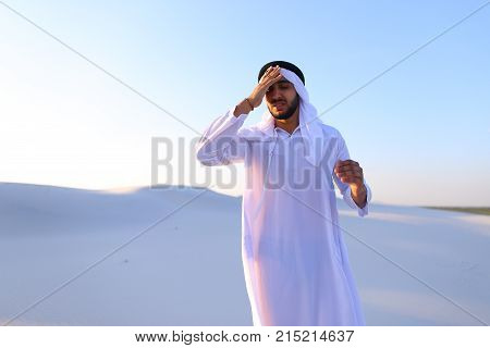 Portrait of tired Arab man, who holds head and feels migraine, tries to calm pain and massages whiskey, standing in middle of bottomless desert with snow-white sand on sunny summer day. Swarthy Muslim with short dark hair dressed in kandura