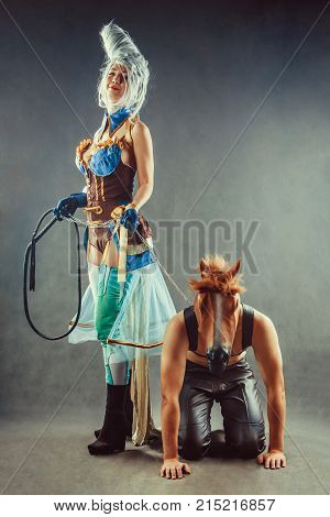 Young Couple In A Role Playing Game, Girl Is Holding A Man In The Horse Mask On The Chain.
