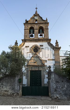Parish church of Sao Romao with a truncated gable showing a rosacea window over the portal double bells clock and a cross in Bacal Braganca Portugal