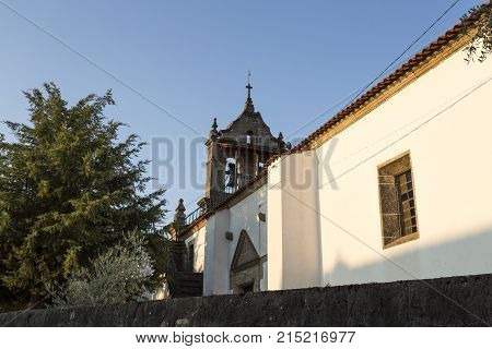 Parish church of Sao Romao with double bells clock and cross on top of a truncated gable in Bacal Braganca Portugal