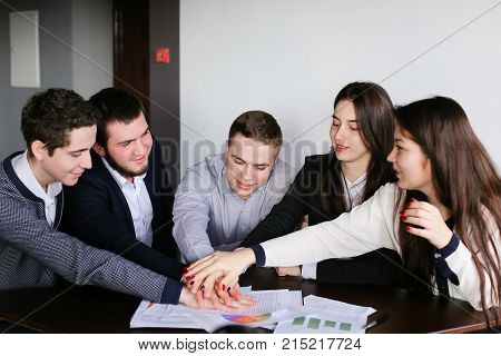 Joyful end of working day in office. Three guys and two girls managers are tuned to positive thoughts and put their hands together on table, loudly scream and enjoy transaction, sitting at desk in office at end of day. Guy with dark curly hair