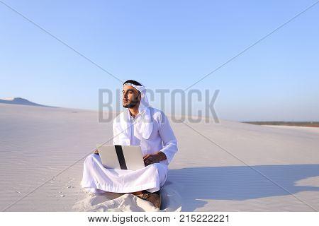 Successful young businessman male Muslim uses laptop to build drawing in Photoshop and prints fingers on laptop sitting on white sand in bottomless wide desert in afternoon against blue sky. Swarthy Muslim with short dark hair dressed in kandura,