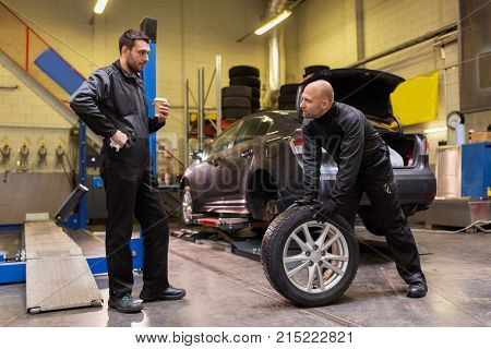 car service, repair, maintenance and people concept - two auto mechanics changing tires at workshop
