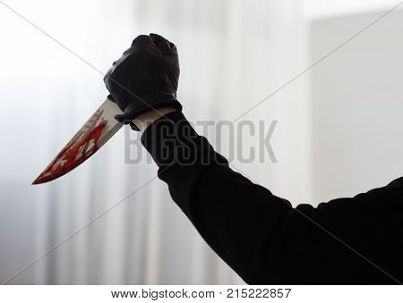 murder and crime scene concept - close up of criminal or murderer hand in leather glove with blood on knife (staged photo)