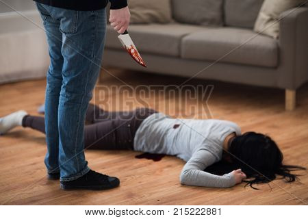 murder, kill and people concept - criminal or murderer with knife in blood and dead woman body lying on floor at crime scene (staged photo)