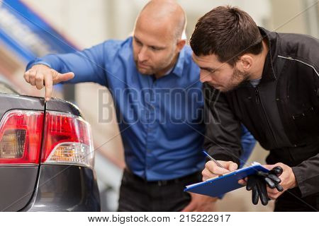 auto service, repair, maintenance and people concept - mechanic with clipboard and customer or car owner looking at taillight at workshop