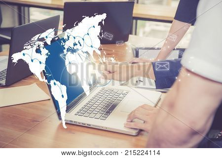 Sending email gesture of finger pressing send button on a computer keyboard on world map with people in office communication concept Elements of this image furnished by NASA.