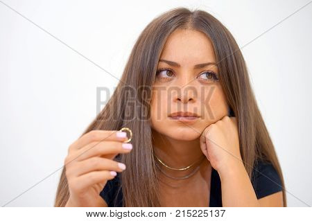 A young woman holding wedding engagement ring in hands engaged girl doubts about marriage proposal abandoned wife depressed after getting divorced help to overcome breaking up starting new life close-up