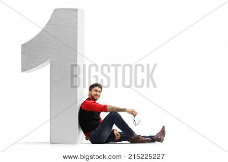 Tattooed guy leaning sitting on the floor and leaning against a cardboard number one isolated on white background