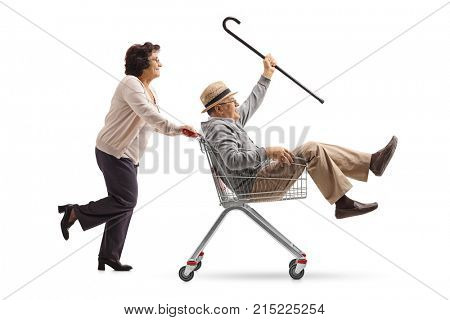 Full length profile shot of an elderly woman pushing a shopping cart with a senior riding inside isolated on white background