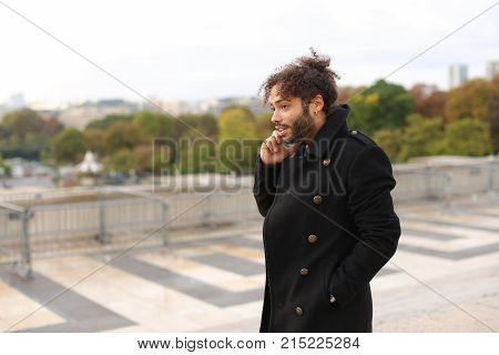 Handsome mulatto tourist using smartphone and enjoying France travel in slow motion.  Attractive guy dressed in black coat with earing and curly hair calling girlfriend. Concept of European trip and advantageous tariff plan.