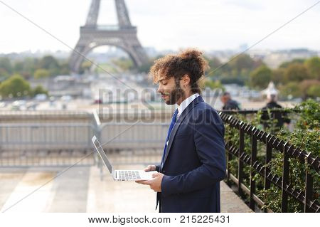 Mulatto administrator of tourist company working on open air with modern laptop near Eiffel Tower in slow motion. Handsome man dressed in black suit, white shirt and blue tie, has dark fleecy hair and beard. Concept of travel agencies and using new techno
