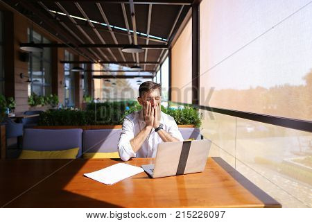 Successful realtor working with laptop at cafe table and typing message to client on smartphone. Handsome gladden male person sitting near green indoor plants. Concept of person as intermediary between sellers and buyers, fast Internet for communicating.