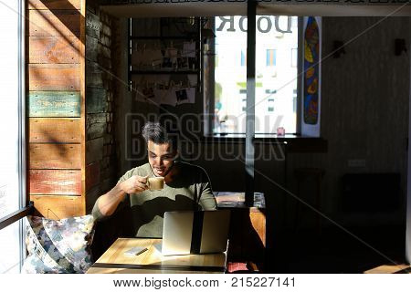 Man takes smartphone from table next to cup of coffee and  modern laptop. Attractive bearded man with dimples dial number and starts conversation. Handsome mulatto talking on phone and working on laptop at same time, presses phone with shoulder.