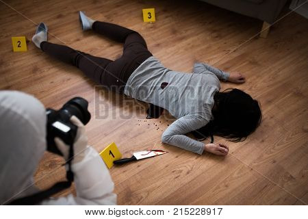 murder, investigation and forensic examination concept - criminalist with camera photographing dead female victim body at crime scene (staged photo)