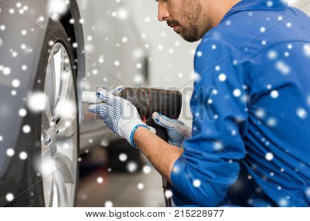 car service, repair, maintenance and people concept - auto mechanic man with screwdriver changing tire at workshop over snow