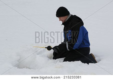 ROVANIEMI, FINLAND - FEBRUARY 17, 2017: Unidentified fisherman during ice fishing on the frozen lake in Lapland, Finland