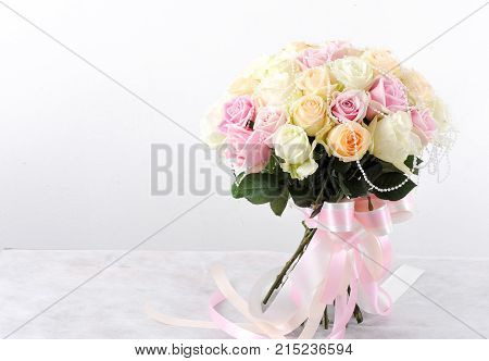Bouquets of roses and ribbon on white background