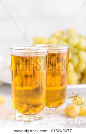 Fresh grape juice in glass and grape on white background