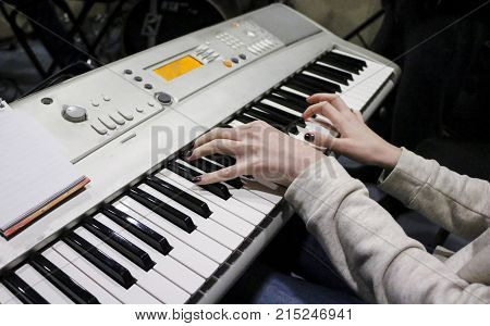 A Young Girl Pianist Plays The Electronic Piano With Her Favorite Music. Female Graceful Hands Touch