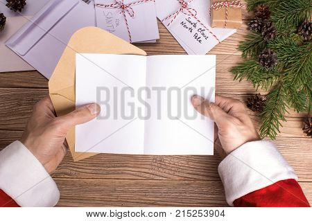 Santa Claus reads letters and holds them in his hands. Mock-up letter format A5
