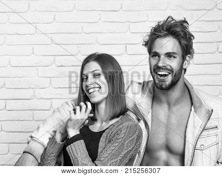 Happy young couple of handsome man or muscular macho in unzipped jacket with pretty cute girl or beautiful woman in knitted coat laugh on white brick background