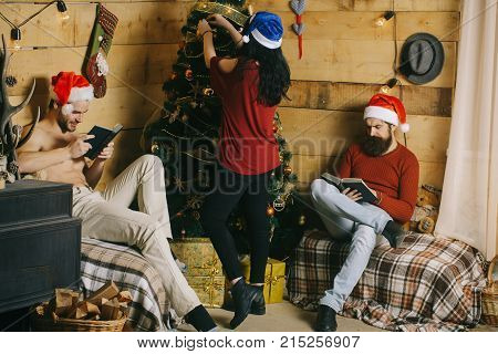 Christmas men and woman read book at tree. Friends in santa hat family and friendship. Xmas party preparation. Winter holiday and celebration. New year man and girl decorate Christmas tree.