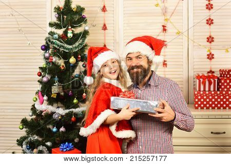 New year small girl man with gift. Xmas party celebration fathers day. Santa kid bearded man at Christmas tree. Christmas happy child and father with present box. Winter holiday and boxing day.