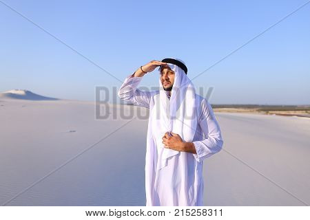 Serious young Arab man peers into distance and tries to see caravan of camels walking, puts hand to forehead defensively against bright sun in hot wide desert with white sand on clear summer day. Swarthy Muslim with short dark hair dressed in kandura