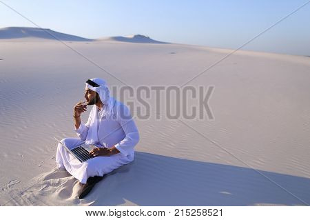 Successful young businessman male Muslim uses laptop to build drawing in Photoshop and prints fingers on laptop sitting on white sand in bottomless wide desert in afternoon against blue sky. Swarthy Muslim with short dark hair dressed in kandura