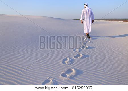 Confident Arabian tourist guy walks on foot along expanses of white sand desert leaving traces on sand. Handsome Emirate smiles widely and spreads hands to sides and whirls around, delighted with landscapes. Swarthy, handsome Muslim with short dark hair