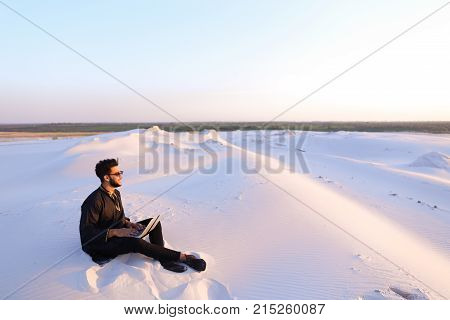 Young and handsome Muslim guy sits in social networks using computer, prints message or reads news, rests from turmoil of city, enjoys tranquility of sandy desert sitting on warm sand in open air on summer evening.