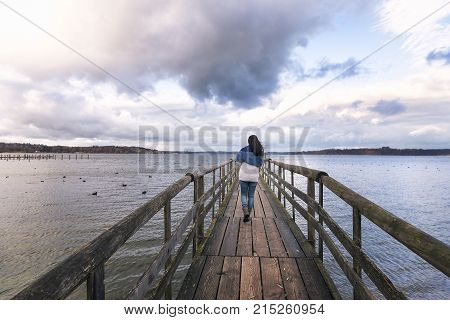 Woman walking on a bridge - Young woman walking alone on a rustic wooden bridge over the Chiemsee lake also called the Bavarian Sea located near Rosenheim Germany.