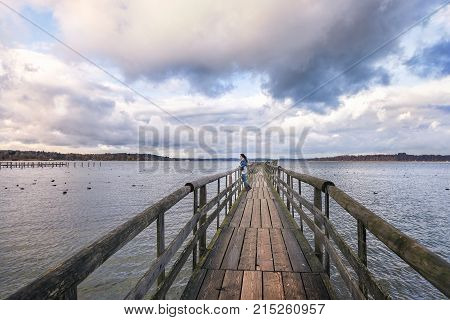 Woman standing on a bridge - Young woman standing on an old wooden bridge meditating and admiring the view of the Chiemsee lake in the afternoon located near Rosenheim Germany.