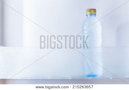a cold bottle of drinking water in refrigerator room for text or copyspace good for clean healthy concept