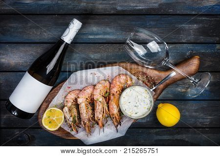Large shrimp or langoustine with white sauce, bottle of wine, glass for the wine and half of a lemon on a wooden board. Top view.